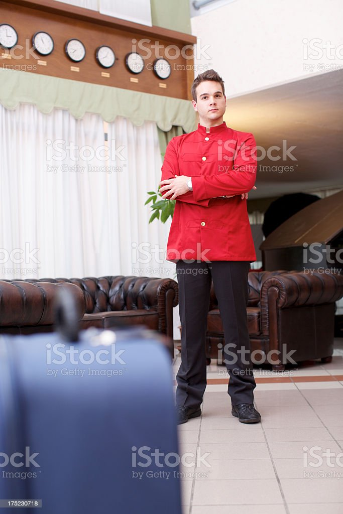 Bellhop standing in hotel lobby royalty-free stock photo