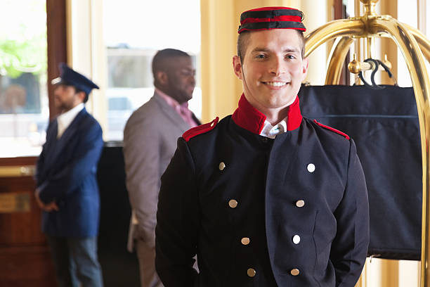 Bellhop standing in hotel lobby with guest's luggage on cart stock photo