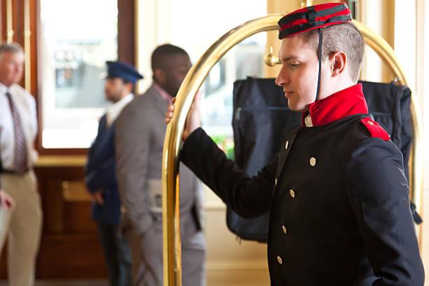 Bellhop con el carro del equipaje espera para los huéspedes del hotel - foto de stock