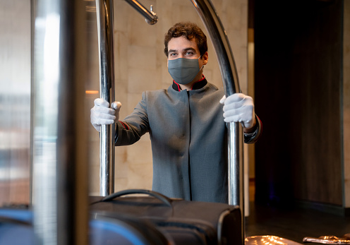 Bellhop working at a hotel wearing a facemask while carrying luggage on a cart during the COVID-19 pandemic