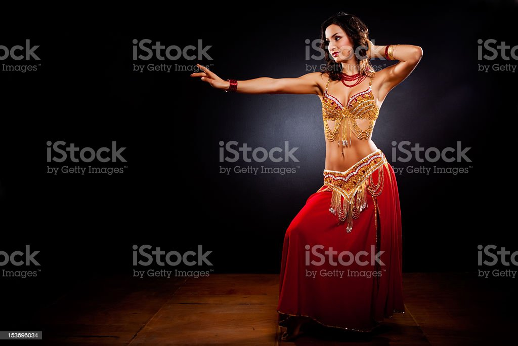 A belly dancer in traditional clothing in a dark studio stock photo