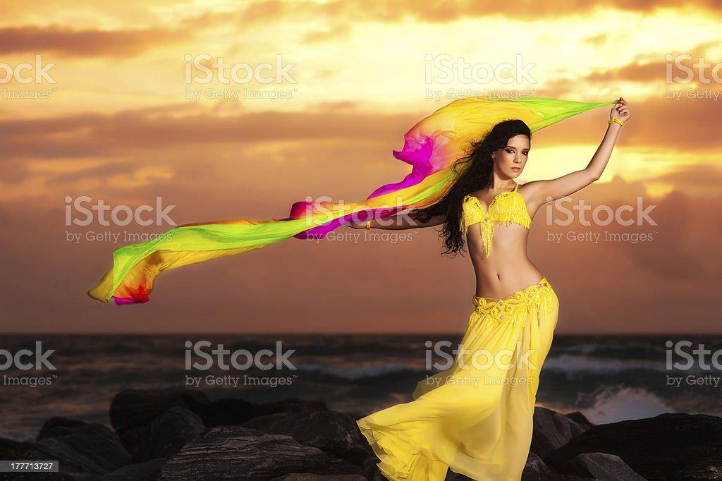 Bauchtänzerin in gelben Badeanzug am Strand bei Sonnenaufgang – Foto
