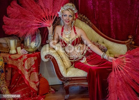 Belly dancer rests with red fans on Chaise Lounge.