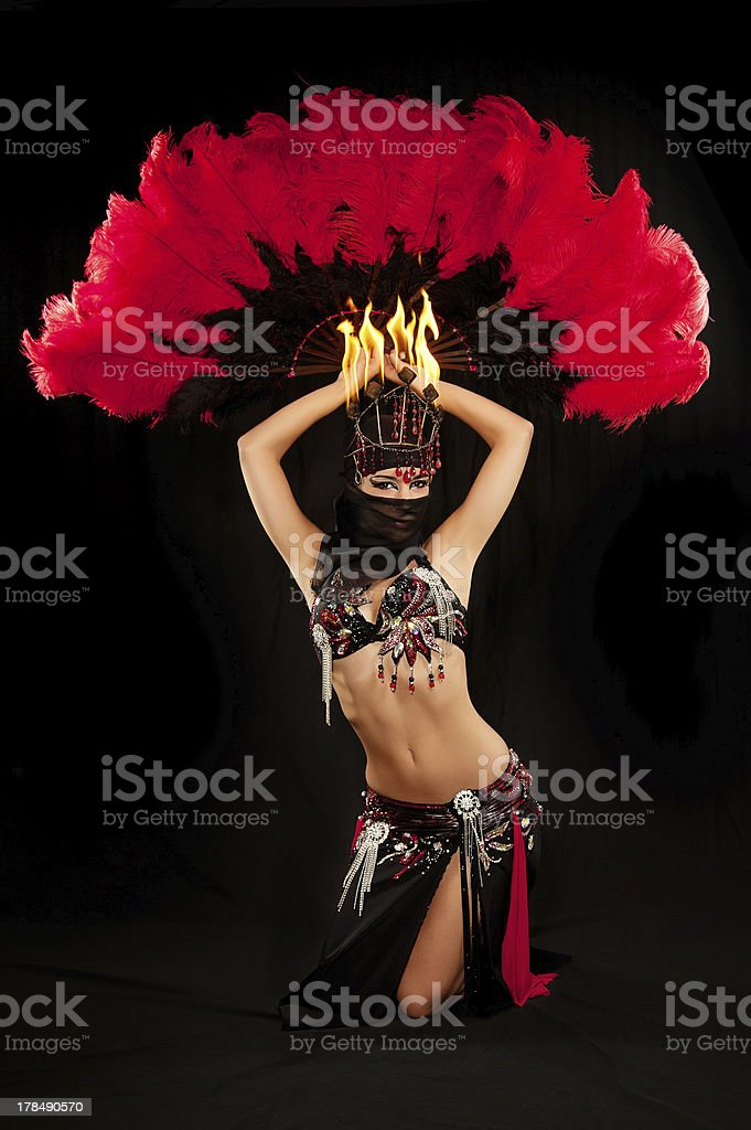 Belly dancer with fire headdress and red feather fan royalty-free stock photo