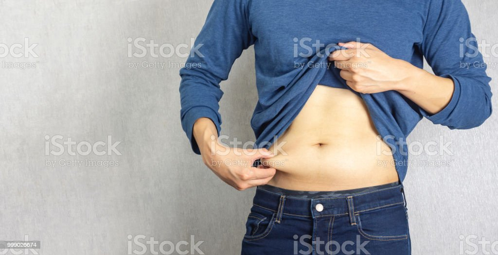 Belly fat pulled by man hand stock photo