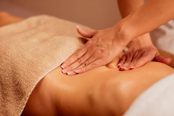 Belly massage. Anti cellulite massage.  Massage Therapist doing healing massage with rolling pin or battledore . Woman enjoying in relaxing massaging at health spa treatment. stock photo