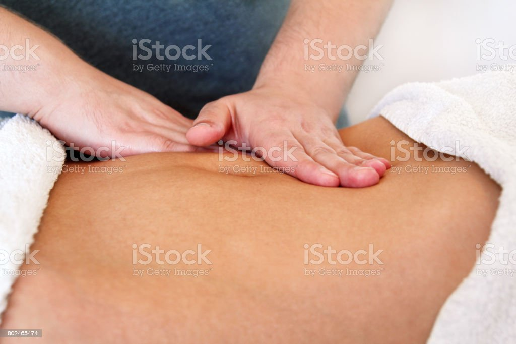 Belly massage in massage studio. Close up of hands massaging female abdomen. Masseur massaging girls belly. Therapist applying pressure on belly. In spa center. Body and health care, medicine concept. stock photo