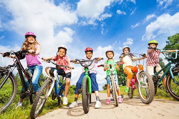 Below angle view of kids in helmets with bikes stock photo