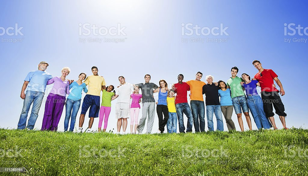 Large group of embraced people against the clear sky. They are...