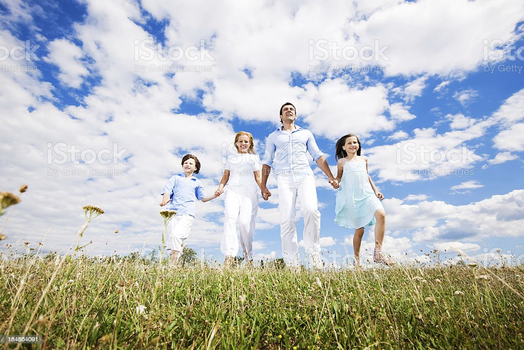Below view of a happy family walking in field. royalty-free stock photo
