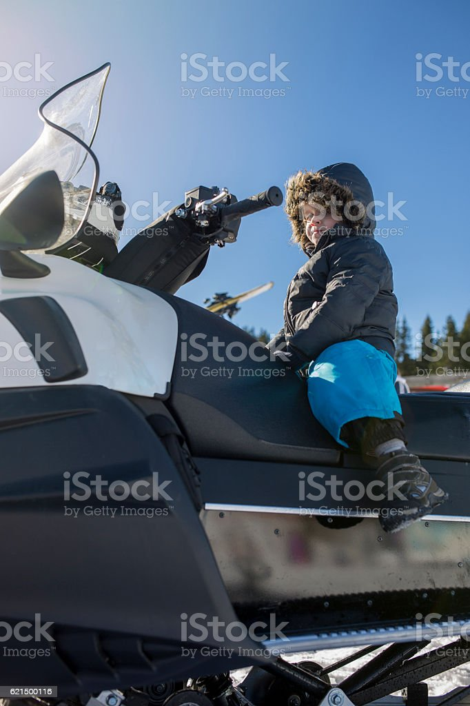 Below view of a small kid sitting on snowmobile. foto stock royalty-free