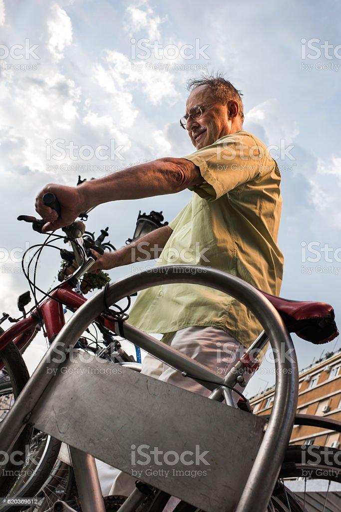 Below view of a smiling senior man parking his bike. zbiór zdjęć royalty-free