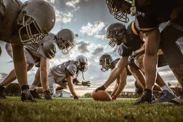 Below view of American football players on a beginning of the match. Low angle view of American football players confronting before the beginning of a match. american football uniform stock pictures, royalty-free photos & images
