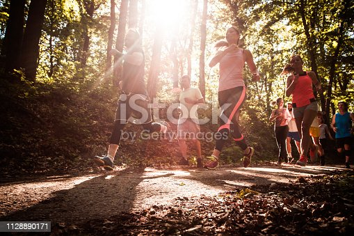 Low angle view of group of mix aged people running a marathon race in nature.