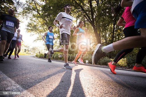 Low angle view of group of athletic people running a marathon race on the road.