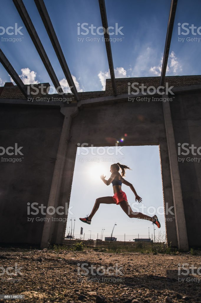 Below view of athletic woman doing a jump while running on a sports training. royalty-free stock photo