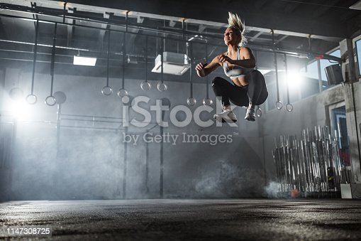 Low angle view of determined athletic woman making an effort while exercising jumps in a health club. Copy space.