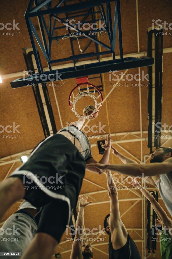 Under beskåda av basketspelare scoring under matchen. - Royaltyfri Aktiv livsstil Bildbanksbilder