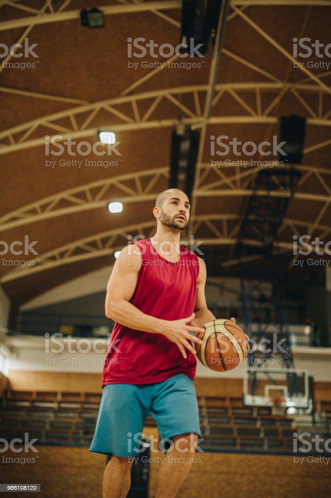 Under beskåda av basketspelare med en boll på en domstol. - Royaltyfri Aktiv livsstil Bildbanksbilder