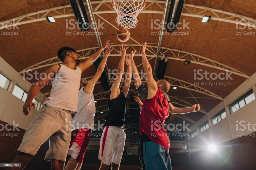 Below view of basketball players in action on the court. - Royalty-free Adulto Foto de stock