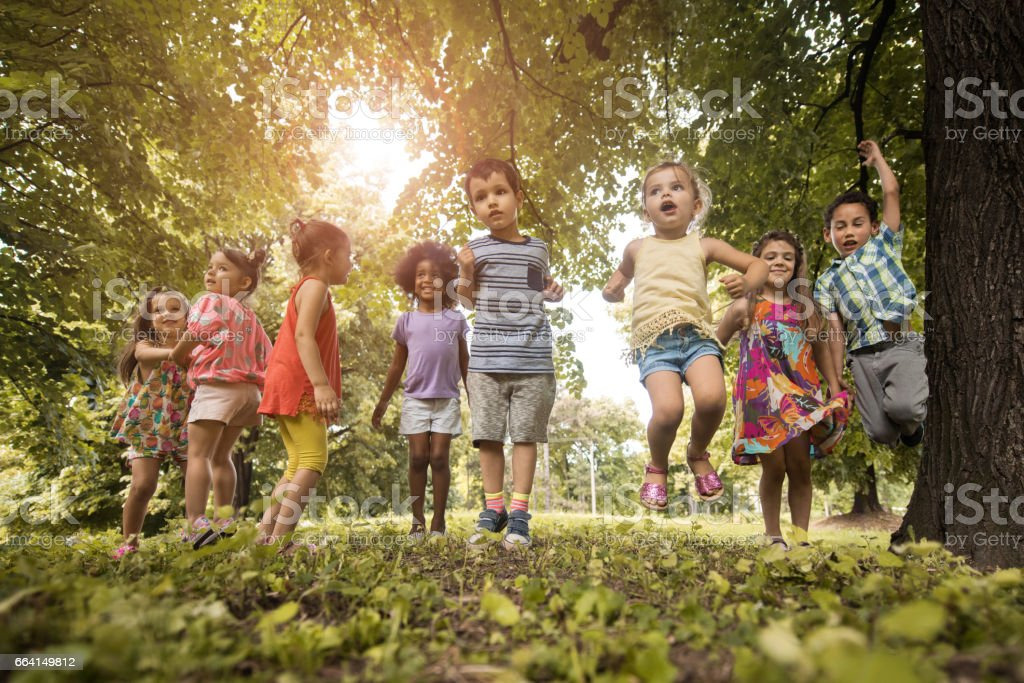 Below view of carefree kids jumping in nature. foto stock royalty-free