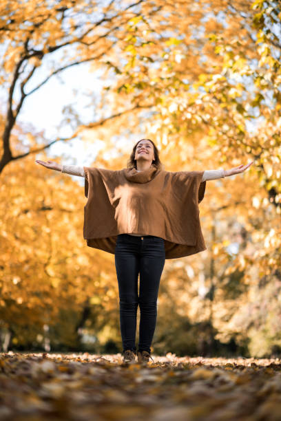 Below view of carefree woman with outstretched arms in the park. stock photo