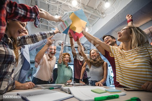 istock Below view of cheerful students and their professor uniting their textbooks. 1000856920