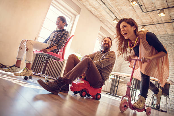 Below view of childish people competing in the office. Low angle view of group of cheerful business friends having fun while behaving childish in the office. They are competing on a chair, toy car and push scooter. young at heart stock pictures, royalty-free photos & images