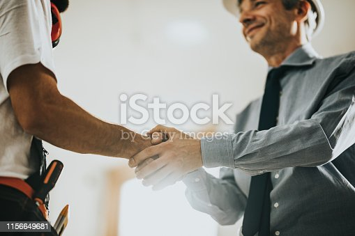 961745166istockphoto Below view of construction worker greeting a foreman at renovating apartment. 1156649681