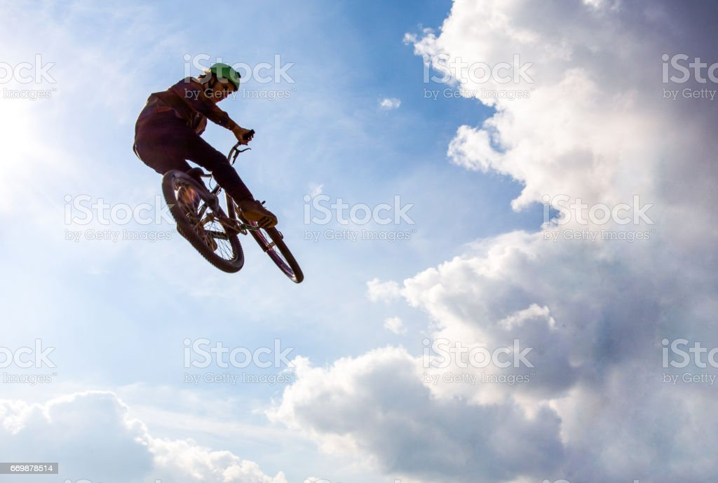 Low angle view of man on mountain bicycle jumping high up against the...