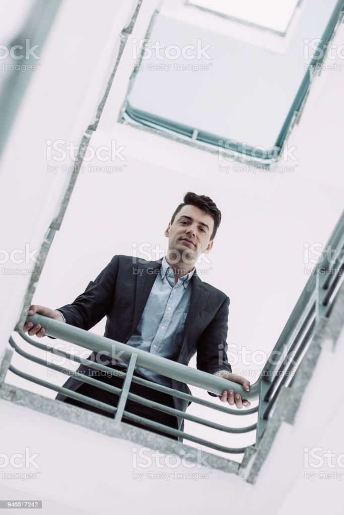 Below view of handsome mid adult manager leaning on railings and looking at camera. Portrait of young businessman looking down in stairwell. Business concept stock photo