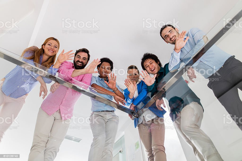 Below view of happy business colleagues waving towards the camera. stock photo