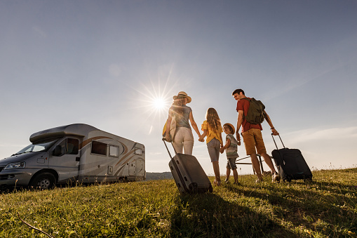 Below view of happy family going on a trip with camp trailer.