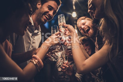 Large group of happy people having fun while toasting with alcohol on a night party.