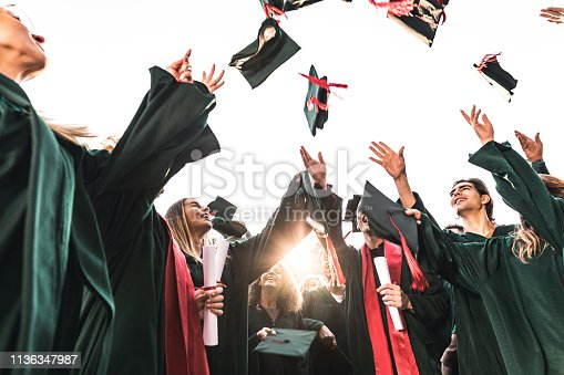 istock Below view of happy graduates throwing their caps up in the air. 1136347987