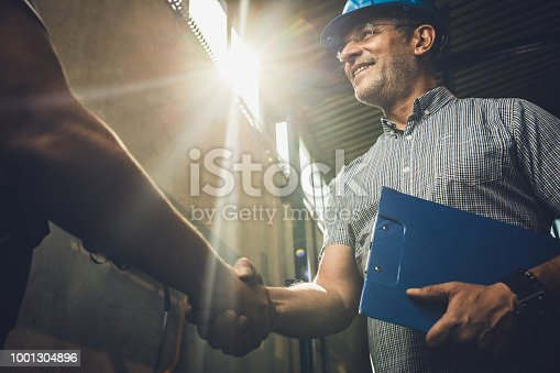 istock Below view of happy inspector shaking hands with unrecognizable person. 1001304896