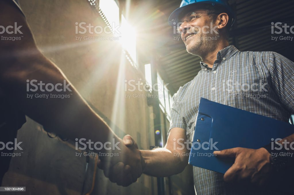 Below view of happy inspector shaking hands with unrecognizable person. stock photo