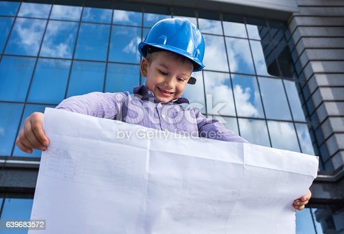 643843490istockphoto Below view of happy little architect looking at blueprints outdoors. 639683572