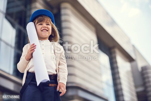 643843490istockphoto Below view of happy little architect with blueprints outdoors. 637745860
