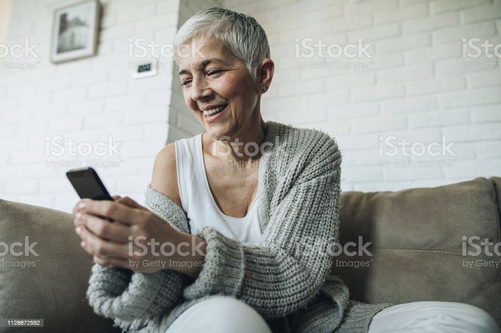 Low angle view of smiling senior woman typing text message on her...