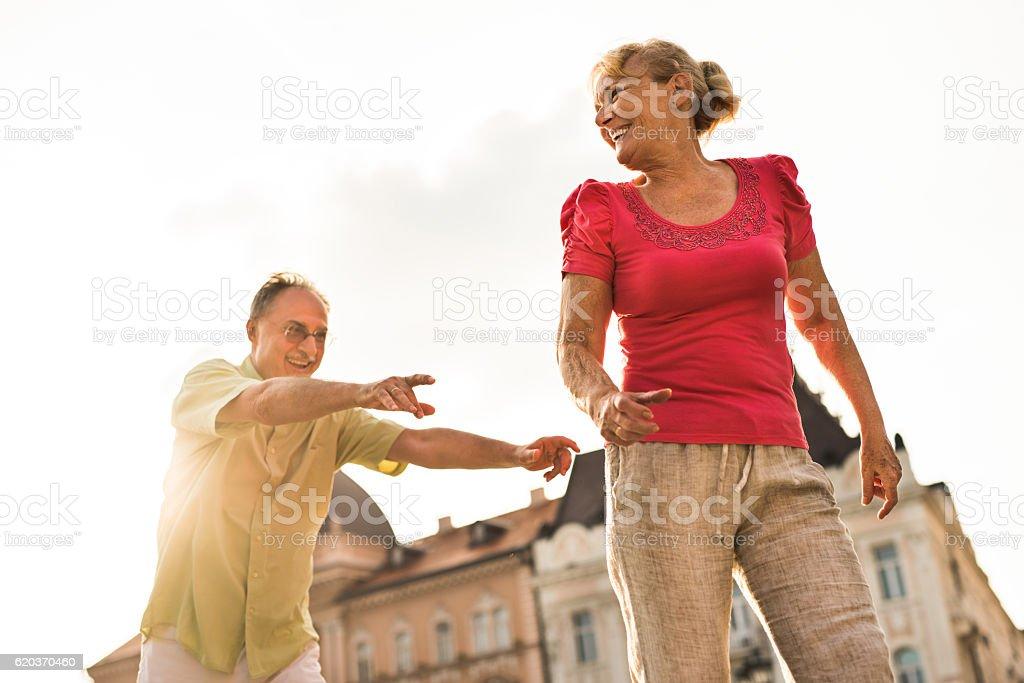 Below view of happy senior couple chasing on sunny day. zbiór zdjęć royalty-free