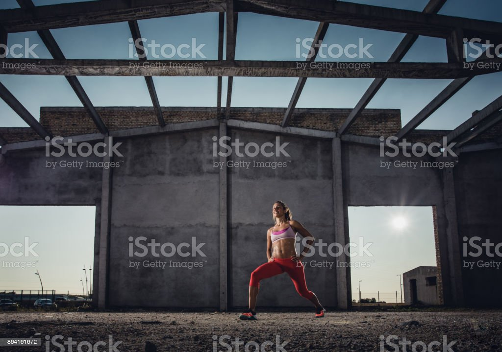 Below view of happy sportswoman doing lunges with her arms akimbo. royalty-free stock photo