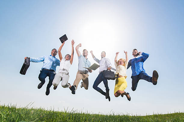 Below view of large business team jumping of joy outdoors. stock photo