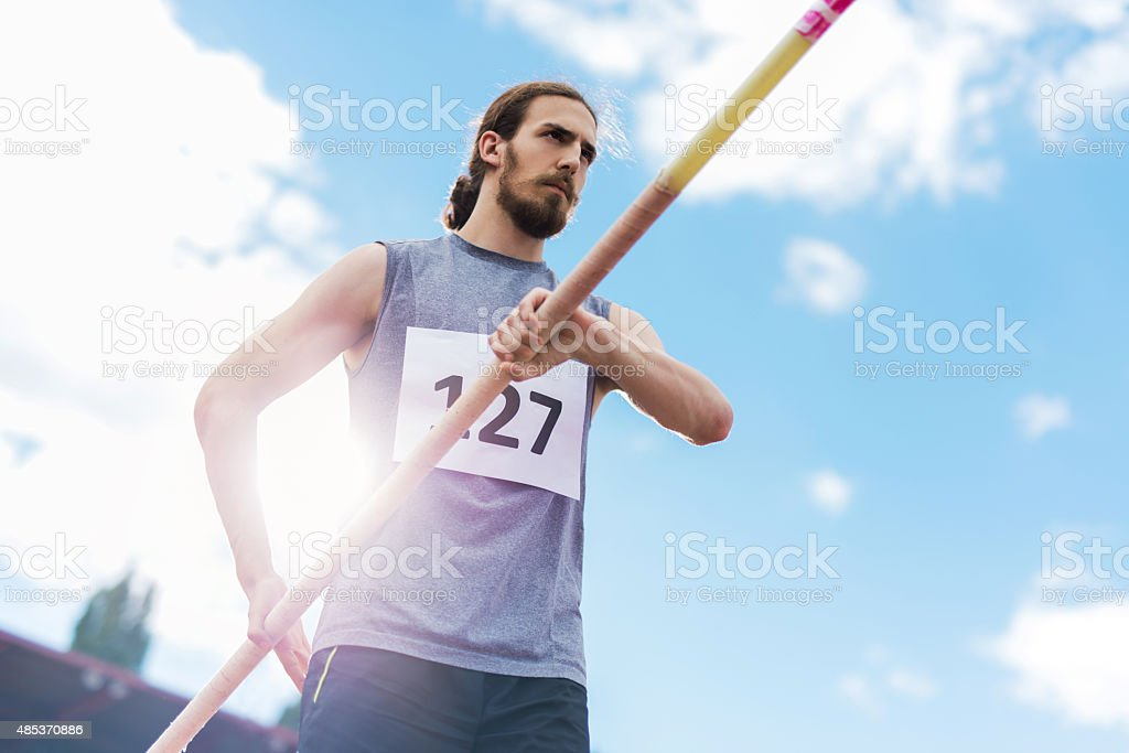 Below view of male athlete preparing for a pole vault. stock photo