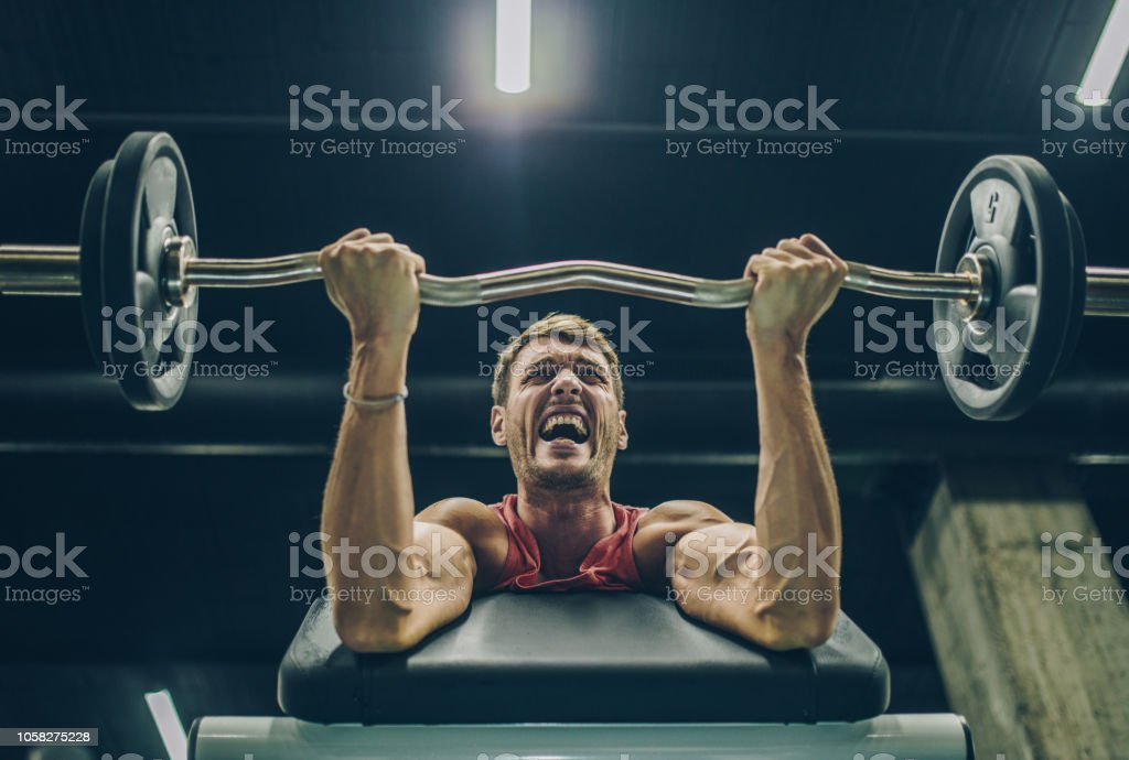 Low angle view of determined athlete making an effort while lifting...