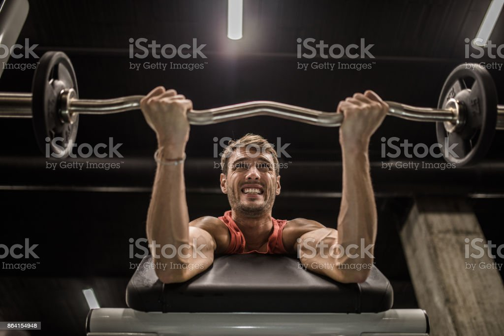 Below view of muscular build man making an effort while exercising with barbell. royalty-free stock photo