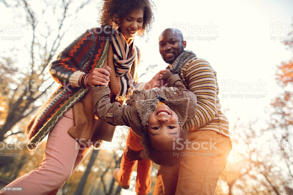 Below view of playful African American family in autumn park. stock photo