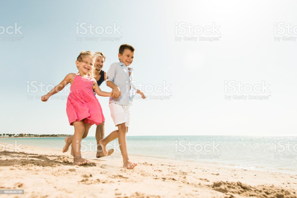 Below view of playful father chasing his kids in summer. royalty-free stock photo