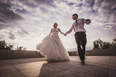 Low angle view of happy married couple having fun on a terrace while holding hands and running.