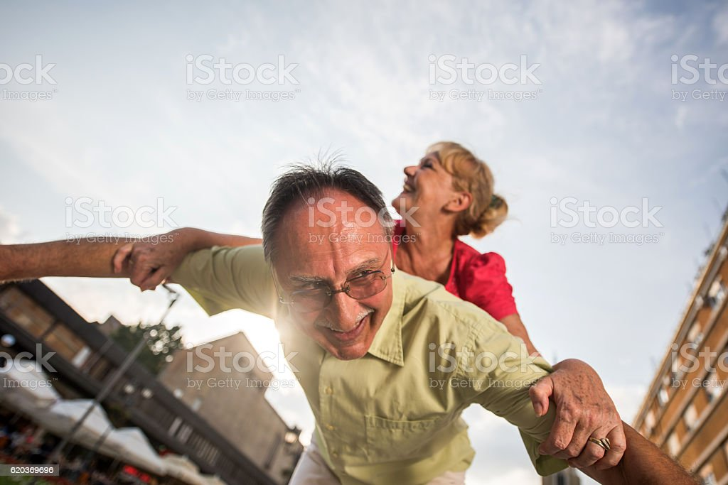 Below view of playful senior couple piggybacking outdoors. foto de stock royalty-free